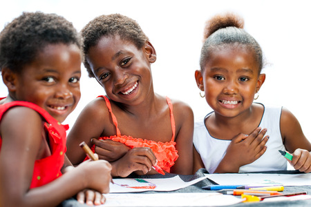 Close up portrait of three cute some African girlfriends drawing together.Isolated on white background. Zdjęcie Seryjne