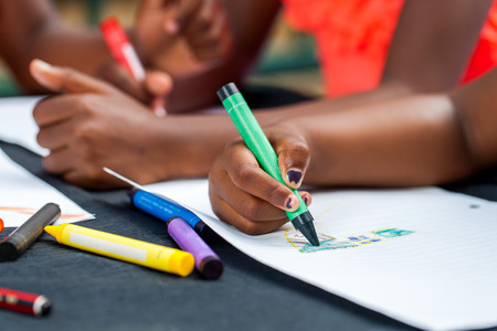 kids activities: Macro close up of African kids hands drawing with wax crayons at desk. Stock Photo