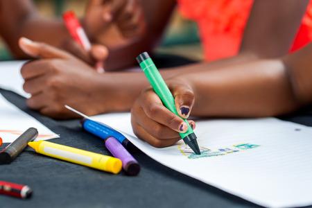 Macro close-up van de Afrikaanse kinderen handen tekenen met waskrijtjes bij bureau.