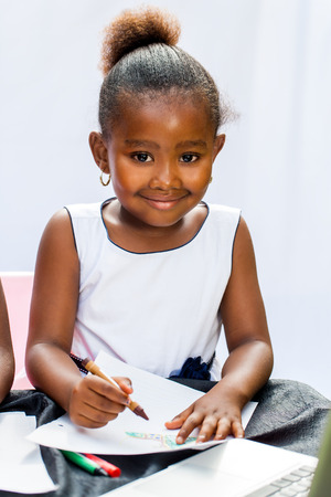 pre school: Close up portrait of little African girl drawing with crayons at desk.Isolated on light background.