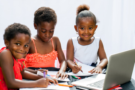 african student: Portrait of three little African girl fiends spending time together drawing with crayons and laptop.Isolated on light background.