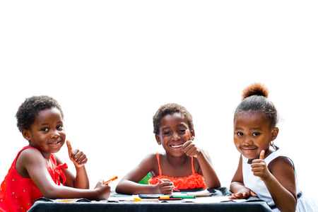thumbs up: Portrait of three African girls doing leisure activity and thumbs up at table.Isolated on white background.