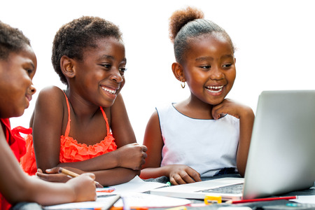 african american ethnicity: Portrait of three little African girls laughing at scene on laptop at desk.Isolated on white background. Stock Photo