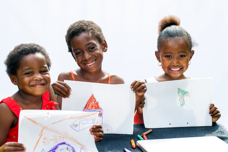 Portrait of three African youngsters showing their drawings at desk.Isolated on light background.