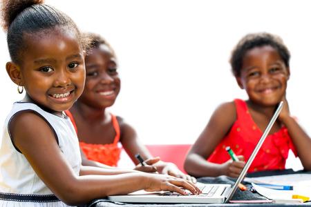 vzdělávací: Portrét trojice afrických dětí s notebookem na table.Isolated na bílém pozadí. Reklamní fotografie