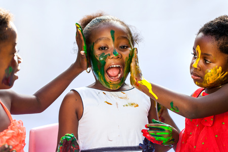 childhood: Portrait of African kids painting themselves with color paint.Isolated against light background.
