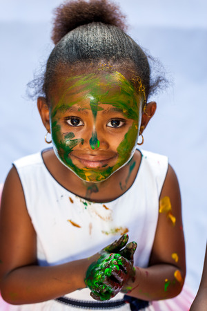 Close up portrait of cute African girl with painted face at painting session.Isolated against light background. Stock Photo
