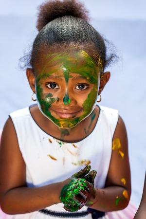 Close up retrato de la niña africana linda con la cara pintada en pintura session.Isolated contra el fondo claro.