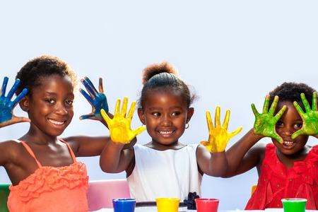 schoolchild: Portret van de Afrikaanse trio tonen geschilderd hands.Isolated tegen de lichte achtergrond. Stockfoto
