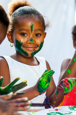 Close up Portrait of African girl painting with friends.Isolated against light background.