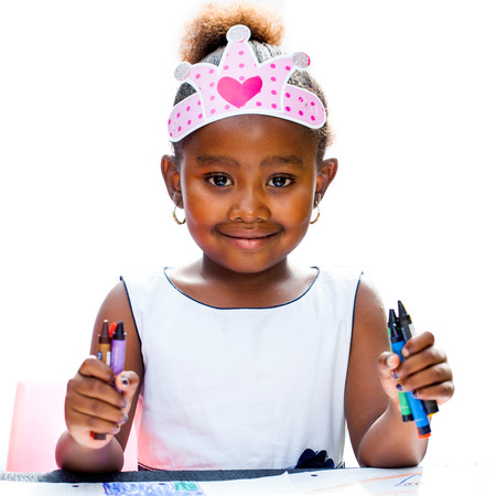 Close up Portrait of Cute afro girl holding wax crayons.Isolated against white background. Stock Photo