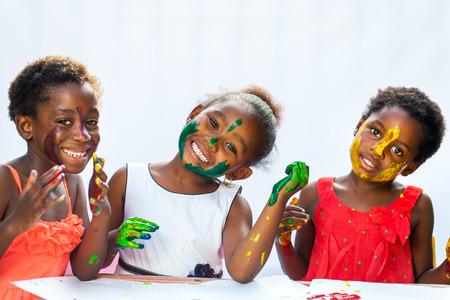 hand schilderen: Portret van de kleine Afrikaanse meisjes die geschilderd faces.Isolated tegen de lichte achtergrond. Stockfoto