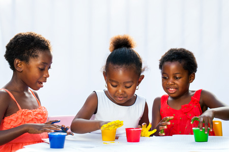 a small painting: Portrait of three African kids painting with hands.Isolated against light background.