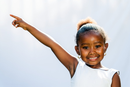 child finger: Portrait of little African girl pointing at corner with finger.Isolated against light background.