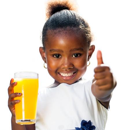 Portret van schattig klein Afrikaans meisje doet duimen omhoog met sinaasappelsap. Geïsoleerd op een witte achtergrond.