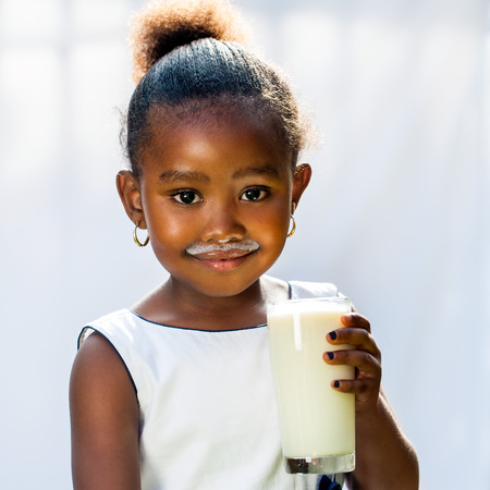 Close up portrait of adorable little African girl drinking glass of milk.Isolated against light background.