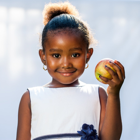 Close up portrait of cute African girl holding apple in hand.Isolated against light background. Stock Photo