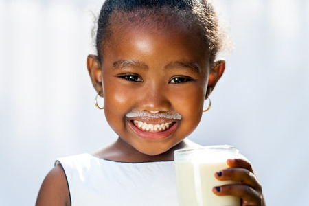 Close up fun portrait of cute African girl showing white milk mustache.Isolated against light background.