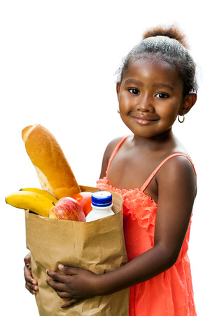 Close up portrait of cute African girl in red dress holding essential groceries in brown bag.Isolated on white background. Banque d'images
