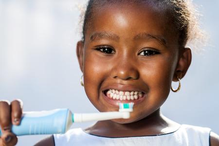 denti: Close up retrato de ni�a linda afro celebraci�n de cepillo de dientes el�ctrico listo para cepillarse los dientes.
