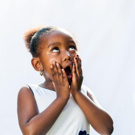 little girl surprised: Portrait of surprised little african girl with hands on face looking up.Isolated against light background. Stock Photo