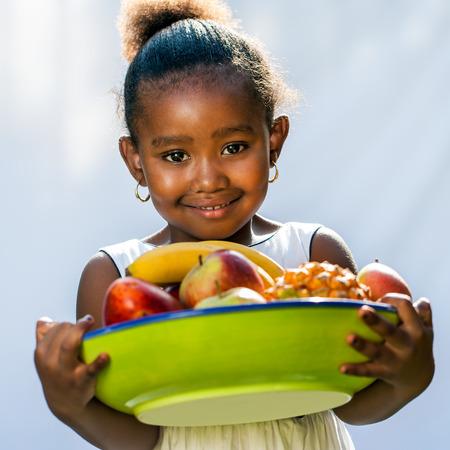アフロアメリカン: 甘いフルーツ ボウルとアフロ アメリカン ガールの肖像画。明るい背景から分離されました。