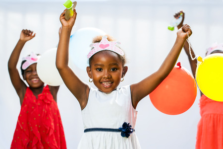 birthday party kids: Close up portrait of cute African girl holding balloons with friends in background.Isolated against light background.