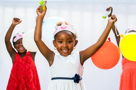 Close-up portret van schattige Afrikaanse meisje bedrijf ballonnen met vrienden in background.Isolated tegen de lichte achtergrond.