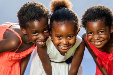 Close up retrato de tres pequeñas niñas africanos felices con las cabezas juntas.