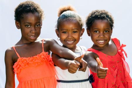 trio: Retrato de las ni�as africanas tr�o haciendo pulgares arriba together.Isolated contra el fondo claro.