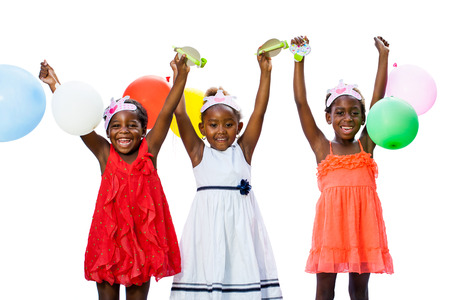 children party: Close up portrait of cheerful threesome African youngsters holding colorful balloons.Isolated against white background. Stock Photo