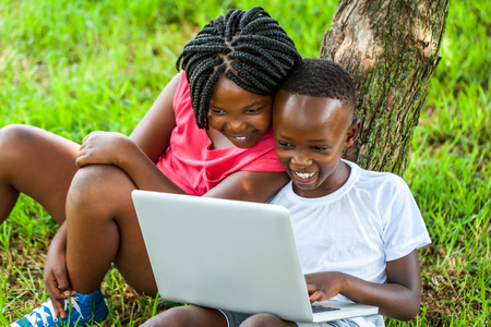 Close up portrait of happy African boy and girl playing on laptop under tree.