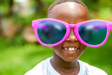 Close up face shot portrait of cute African boy wearing huge over sized sun glasses outdoors.