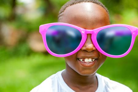 Close-up gezicht geschoten portret van schattige Afrikaanse jongen het dragen van enorme extra grote zonnebril buitenshuis. Stockfoto