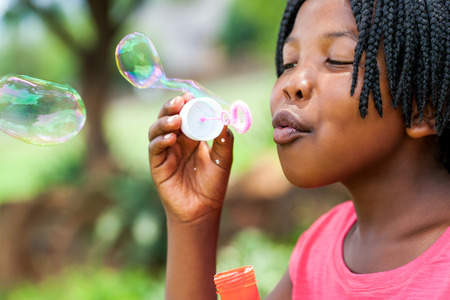 kid smile: Close up portrait of cute African girl with braids blowing bubbles in park.