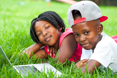 africa american: Close up portrait of African boy and girl laying on green grass with laptop.