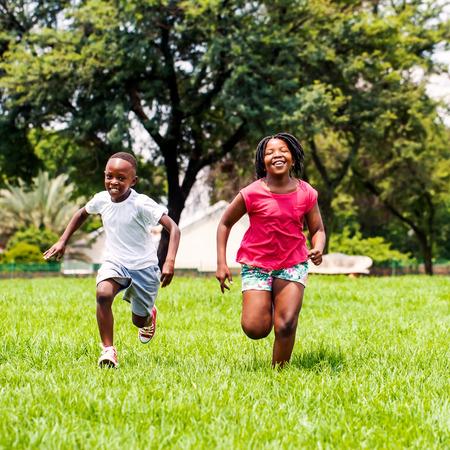 Aktionsporträt von den afrikanischen Kindern, die zusammen in Park spielen und laufen.
