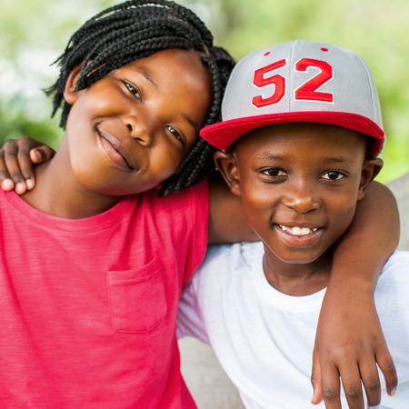 Schließen Sie herauf das Gesicht, das draußen vom lächelnden afrikanischen Jungen und vom Mädchen geschossen wird. Standard-Bild