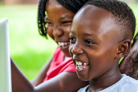 Close up face shot of African kids laughing at movie scene on digital tablet outdoors.