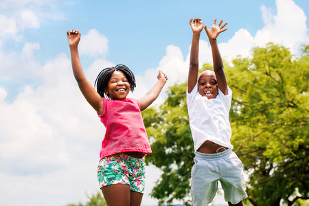 children face: Action portrait of young African boy and girl jumping in park. Stock Photo