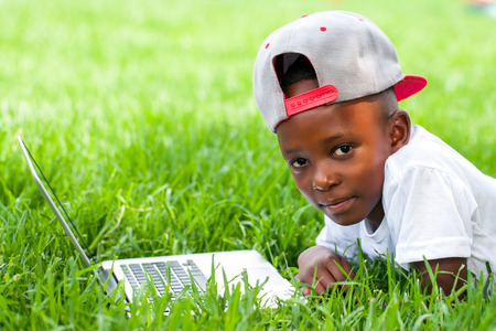 Close up portrait of African boy with baseball hat laying with laptop on grass.