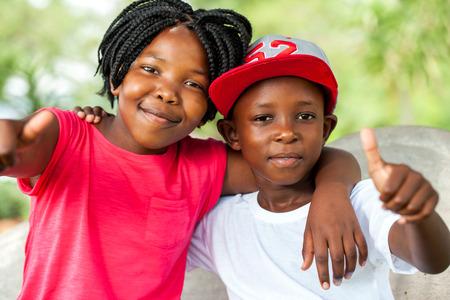 Close up retrato al aire libre del hermano y hermana africana que hace los pulgares para arriba.