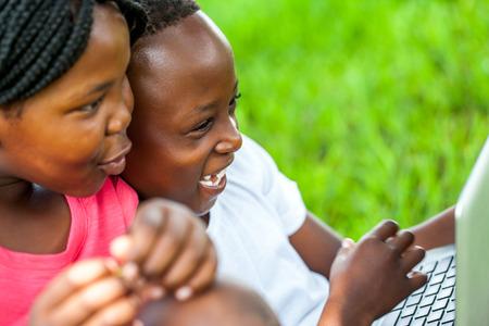 niños negros: Cierre de la cara del tiro de los niños africanos que se ríen de escena en la computadora portátil al aire libre.
