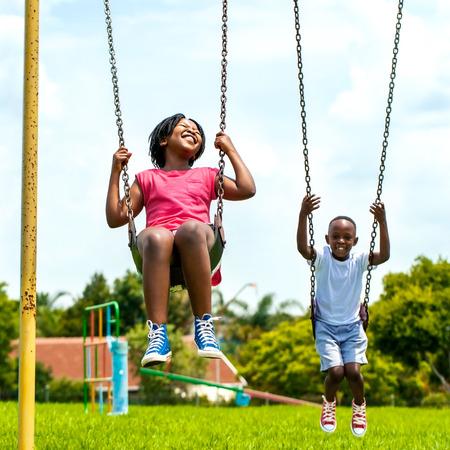 playground children: Retrato de Acci�n de ni�os africanos que se divierten oscilante en park.Out de casas foco en el fondo. Foto de archivo