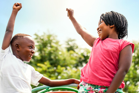Close up portrait of two happy African kids looking at each other raising hands outdoors. Archivio Fotografico
