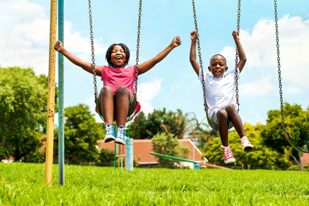 children face: Action portrait of shouting African kids playing on swing in neighborhood.Out of focus houses in background. Stock Photo