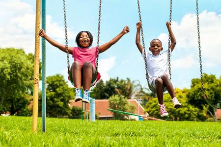 dětské hřiště: Akce portrét křik africké děti si hrají na houpačce v neighborhood.Out cílových domů v pozadí.