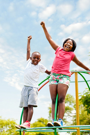 Full length portrait of two African kids shouting and raising hands in park.