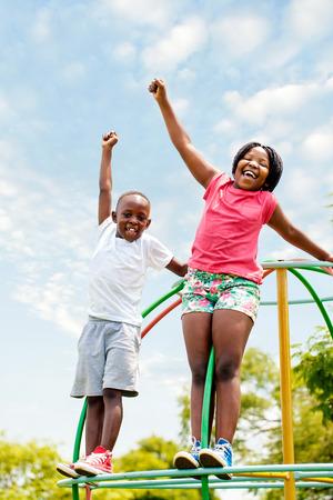 hermanos jugando: Retrato de cuerpo entero de dos ni�os africanos gritando y levantando las manos en el parque. Foto de archivo