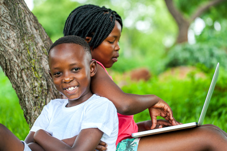 pre adolescent boy: Close up portrait of happy African kids under tree playing on laptop.